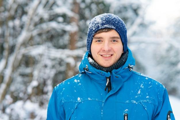 Cara feliz, jovem sorrindo no fundo de uma floresta de inverno na neve.