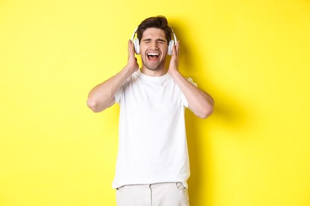 Cara feliz ouvindo música em fones de ouvido novos, comprando fones de ouvido na sexta-feira negra, em pé sobre a parede amarela