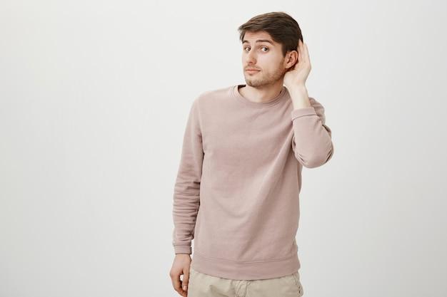 Cara fofo intrigado escutando, segure a mão perto da orelha