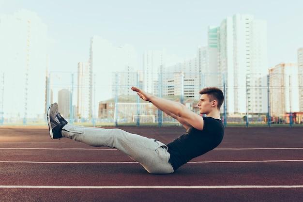 Cara forte com um bom corpo pela manhã no estádio. ele usa roupas esportivas, fazendo exercícios. ele parece tenso.