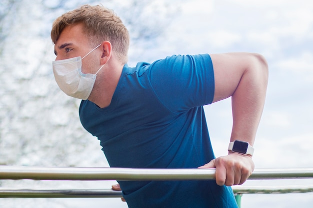 Cara forte, jovem atlético na máscara protetora médica fazendo esporte exercício, flexões nas barras assimétricas, treino ao ar livre durante a quarentena. estilo de vida saudável, coronavírus, conceito de covid-19