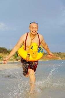 Cara gay corre na água com um anel de borracha amarelo