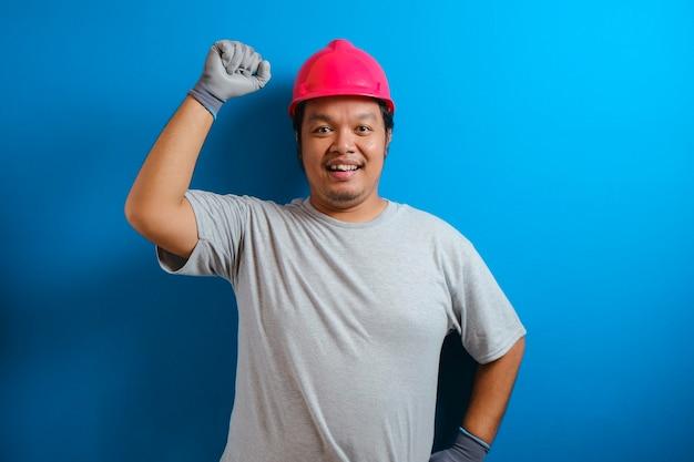 Cara gordo asiático usando um capacete, olhando para a câmera enquanto aperta as mãos para cima. o homem mostrou um gesto de vitória
