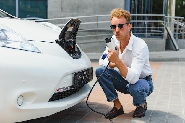 Cara hansome sentado perto de seu novo carro elétrico moderno e segurando o plugue do carregador, enquanto o carro carrega na estação de carregamento