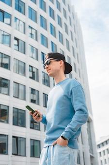 Cara hipster positivo com mochila em pé ao ar livre segurando o smartphone enquanto desvia o olhar com um sorriso