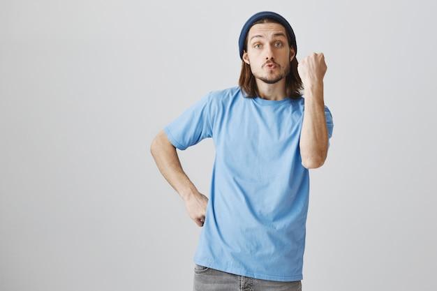 Cara hipster sacudindo o punho, ameaçando e repreendendo pessoa