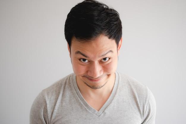 Cara inábil complicado engraçada do sorriso do homem no t-shirt cinzento.