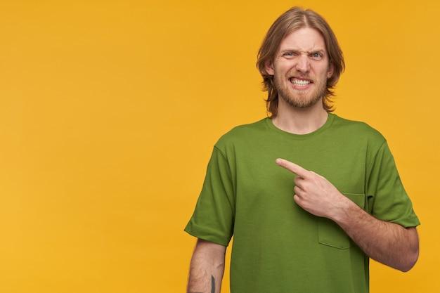 Cara irritado e inseguro com cabelo loiro e barba. vestindo uma camiseta verde. tem tatuagem. seu rosto torto. e apontando o dedo para a esquerda no espaço da cópia, isolado sobre a parede amarela