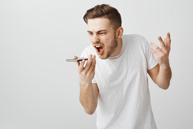 Cara irritado e irritado gritando com alto-falante do celular, grave mensagem de voz furiosa