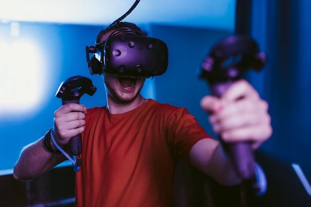 Cara jogando um jogo de tiro online na sala de néon do jogo