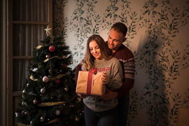 Cara jovem, abraçando-se de volta alegre senhora com caixa de presente perto de árvore de natal