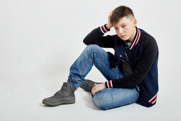 Cara jovem adolescente senta-se em jeans azul no chão