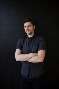 Cara jovem adulto em uma camisa cinza. retrato de negócios em preto texturizado