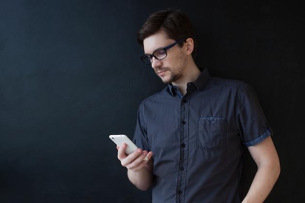 Cara jovem adulto em uma camisa cinza usa um smartphone. retrato de negócios em preto texturizado