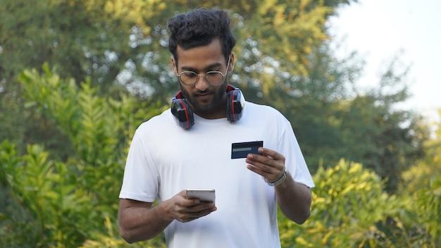Cara jovem alegre em camisa casual, t-shirt branca posando isolado. conceito de estilo de vida de pessoas. usando o celular, retenha o cartão do banco