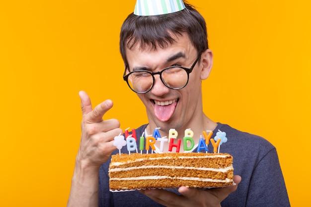 Cara jovem alegre louco com óculos, segurando uma vela acesa nas mãos e um bolo de felicitações em uma parede amarela. conceito de celebração de aniversário e aniversário.