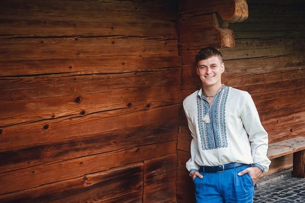 Cara jovem bonita com uma camisa bordada no fundo de uma casa de madeira.