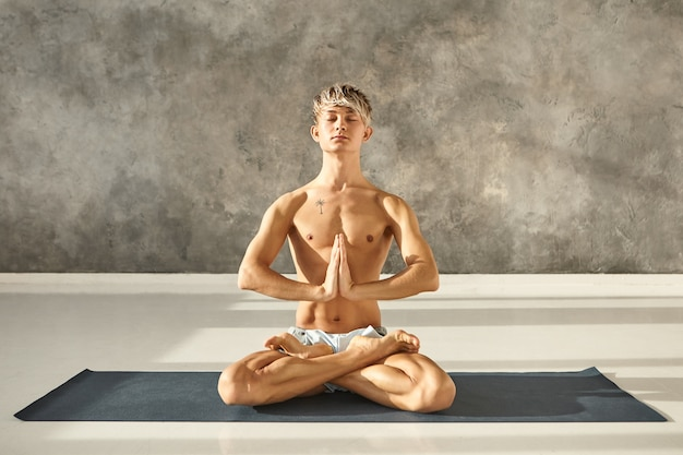 Cara jovem bonito com cabelo loiro e tatuagem no torso nu, sentado no tapete de ioga em pose de lótus, fazendo sukhasana, fechando os olhos e pressionando as mãos em namaste. meditação e concentração