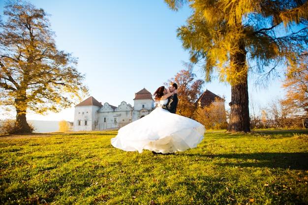 Cara jovem bonito com menina morena nos braços. os noivos românticos dançam no parque.