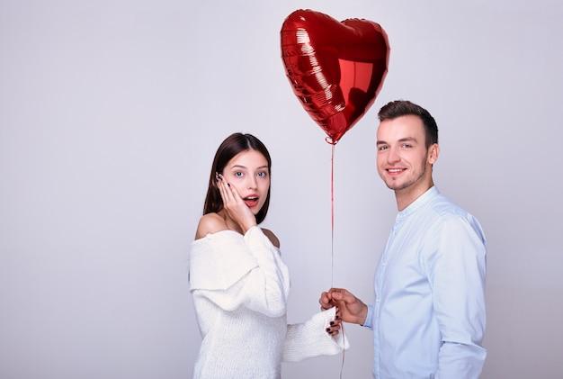 Cara jovem bonito dá um balão de coração vermelho.
