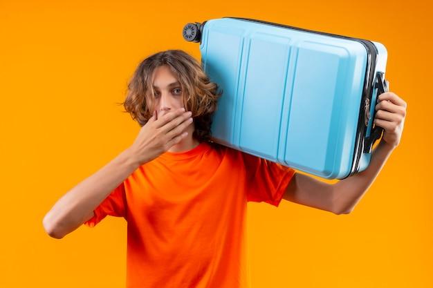 Cara jovem bonito de camiseta laranja, segurando a mala de viagem, olhando surpreso e espantado, cobrindo a boca com a mão