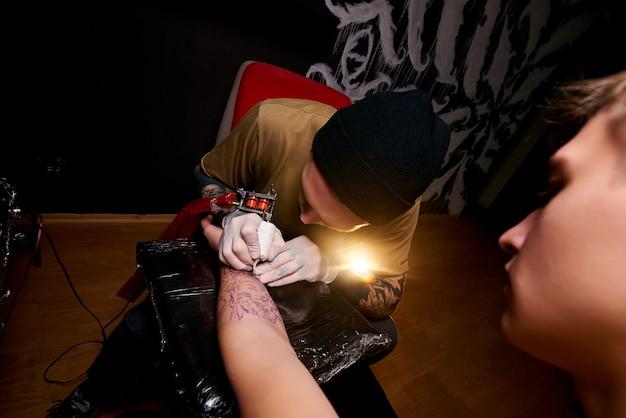Cara jovem bonito em um chapéu preto e com tatuagens