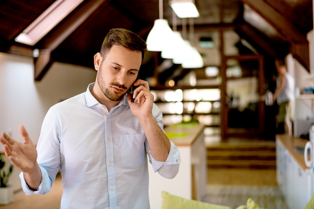 Cara jovem bonito falando no celular em casa
