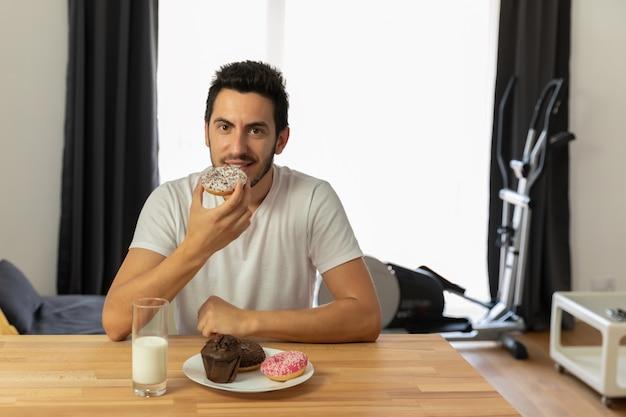 Cara jovem bonito se senta em uma mesa e come rosquinhas.