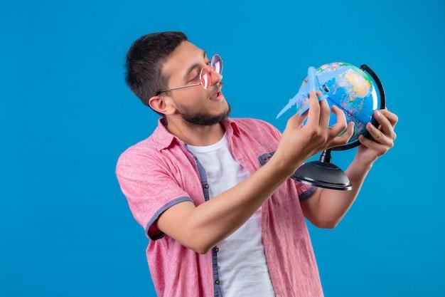 Cara jovem bonito viajante segurando usando óculos escuros, segurando o avião de brinquedo e globo jogando feliz e positivo em pé sobre fundo azul