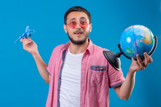 Cara jovem bonito viajante segurando usando óculos escuros, segurando o avião de brinquedo e globo olhando positivo e feliz sorrindo amigável em pé sobre fundo azul
