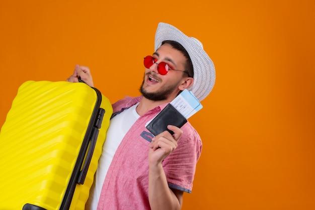 Cara jovem bonito viajante usando óculos escuros no chapéu de verão segurando bilhetes mala e ar, olhando confiante e feliz sorrindo alegremente pronto para viajar em pé sobre fundo laranja