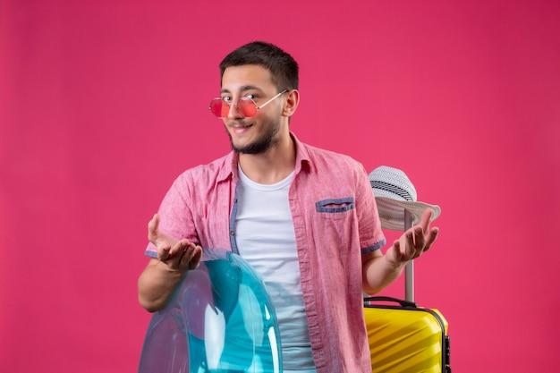Cara jovem bonito viajante usando óculos escuros, segurando o anel inflável em pé com mala de viagem, olhando para a câmera slyly sorrindo com os braços levantados sobre fundo rosa