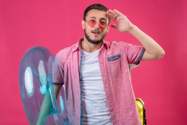 Cara jovem bonito viajante usando óculos escuros, segurando o anel inflável, olhando para a câmera positiva e feliz saudando em pé sobre fundo rosa