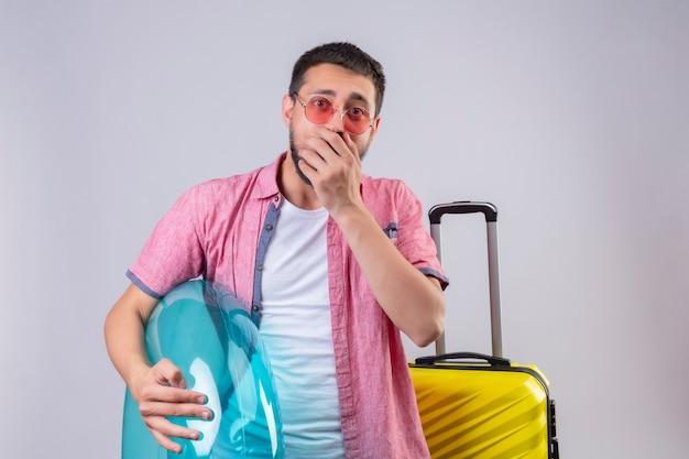 Cara jovem bonito viajante usando óculos escuros, segurando o anel inflável, olhando para a câmera surpreendida e espantada, cobrindo a boca com a mão em pé com mala de viagem, sobre fundo branco