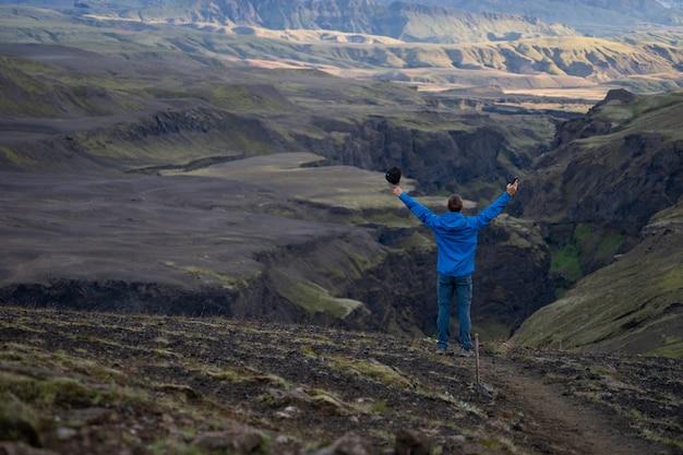 Cara jovem caucasiano em pé sobre fundo de montanha e desfiladeiro no caminho da trilha laugavegur, islândia. promover um estilo de vida saudável.