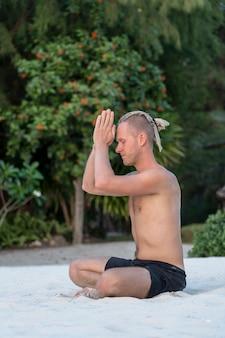 Cara jovem com dreadlocks fazendo ioga em uma praia tropical, close-up. o conceito de um estilo de vida saudável