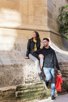 Cara jovem com pacotes abraçando feliz senhora sentada na pedra