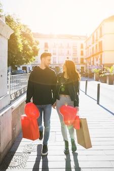 Cara jovem com pacotes e balão de mãos dadas com a senhora sorridente na rua