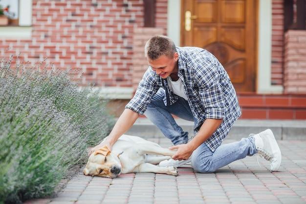 Cara jovem com retriever em caminhada no pátio de verão. homem bonito acariciando seu retriever dourado na frente da casa.