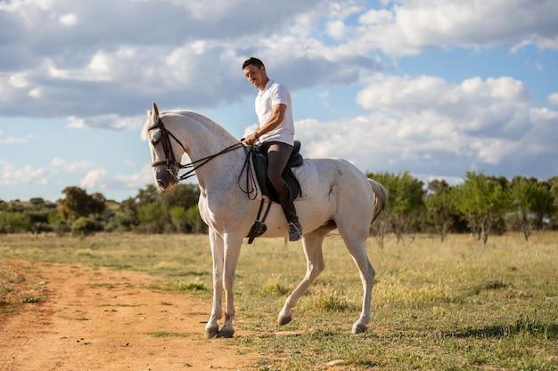 Cara jovem com roupa casual, andar a cavalo branco na estrada arenosa