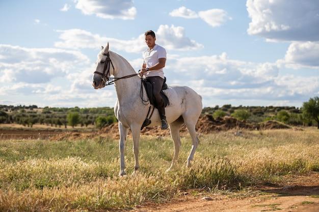 Cara jovem com roupa casual, andar a cavalo branco no prado, um dia ensolarado