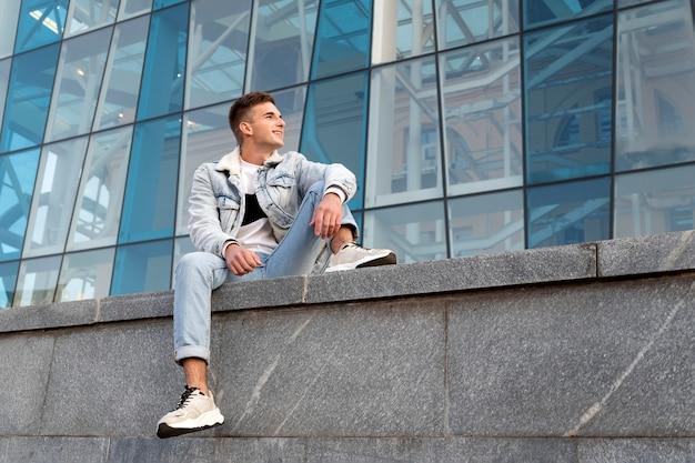 Cara jovem com roupas elegantes senta-se no fundo da fachada de vidro. menino incrível feliz descansando na cidade.