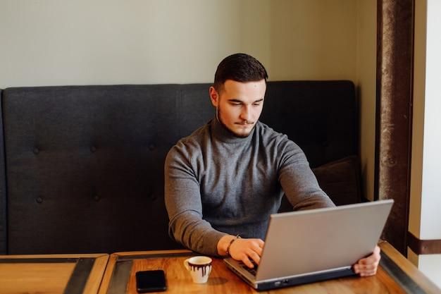 Cara jovem com seu telefone celular e tomando um café. homem da moda jovem café expresso no café da cidade durante a hora do almoço e trabalhando em um computador laptop