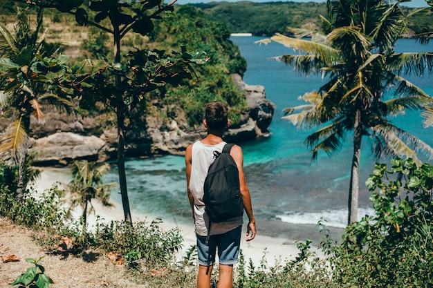 Cara jovem, com uma barba e uma mochila posando na selva em um boné