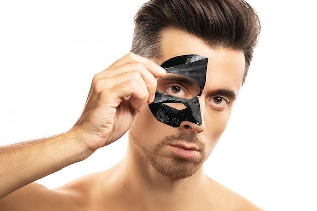 Cara jovem com uma máscara de carvão preto no rosto em branco.