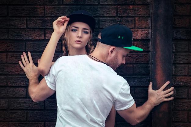 Cara jovem de calça preta e uma camiseta branca posa com uma linda garota loira ao ar livre.