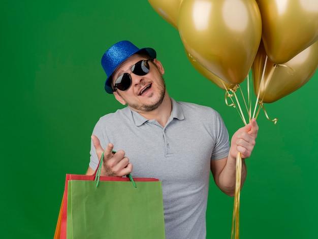 Cara jovem de festa descontente inclinando a cabeça usando chapéu de festa e óculos segurando balões com sacolas de presente isoladas no verde