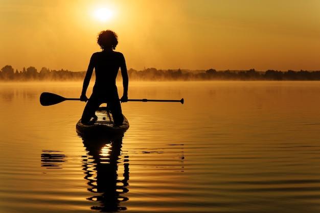 Cara jovem desportivo em silhueta nadando a bordo de sup com remo longo.