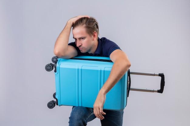Cara jovem e bonito viajante parado com uma mala estressante, mantendo as mãos na cabeça cansada e frustrada sobre um fundo branco