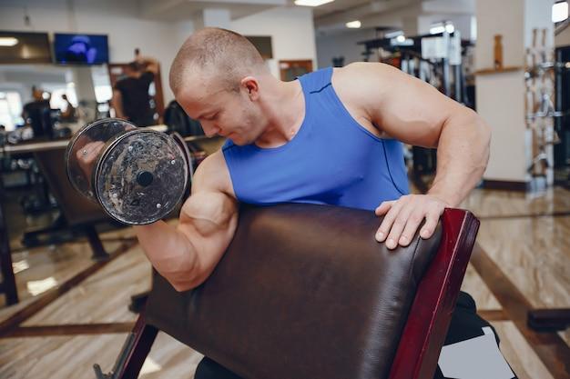 Cara jovem e forte treina no ginásio